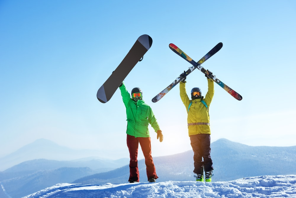 Skier and snowboarder on a snowy mountain
