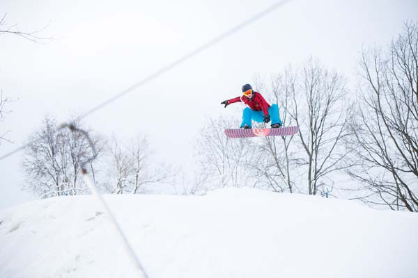 snowboarder jumping on snowy hill